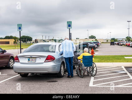 An elderly man prepares to help his disabled wife into their automobile in a parking lot in Oklahoma City, Oklahoma, - Stock Photo