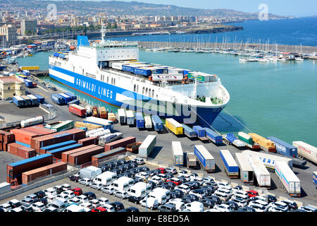 New cars & vans on Catania port dockside jetty with Grimaldi Lines 'Eurocargo Livorno' top deck being loaded with - Stock Photo
