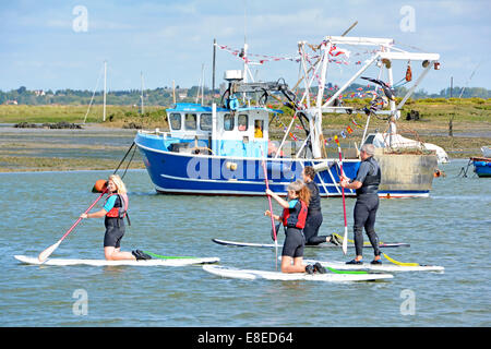 Group of people paddle boarding by kneeling on the board with one man standing - Stock Photo