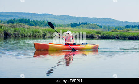 Young Woman Kayaking Alone on a Calm River and Wearing a Safety Vest - Stock Photo