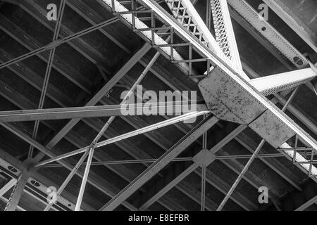 Underside of a riveted and bolted bridge structure - Stock Photo