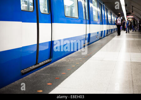 Colorful Underground Subway Train with blurry People on the Platform. Focus is on the door. room for your text. - Stock Photo