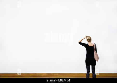 Caucasian Young Blond Woman Questioning in front of a Blank Wall in a Museum - Stock Photo
