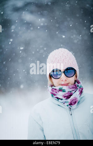 Happy Cute Woman Enjoying Winter during a Snowy Day - Stock Photo