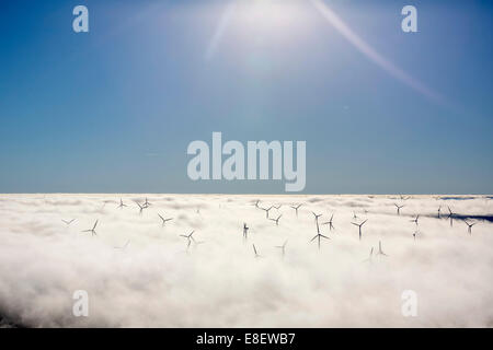Wind turbines covered by low clouds, blue sky, aerial view, Marsberg, Sauerland region, North Rhine-Westphalia, - Stock Photo
