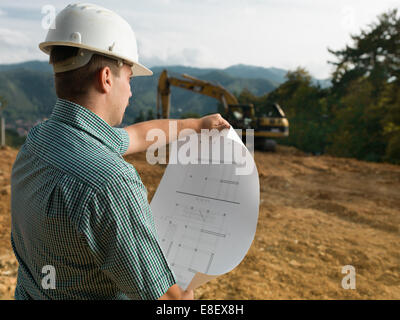 back view of male engineer standing on construction site reading blueprint - Stock Photo