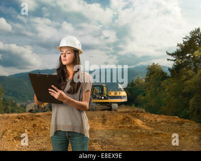 portrait of young caucasian female architect standing on construction site, holding clipboard and writing - Stock Photo