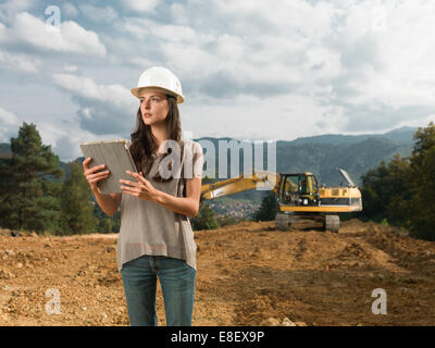 portrait of young caucasian female engineer standing on construction site, holding digital tablet, looking away - Stock Photo