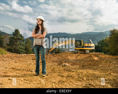 female engineer standing with her arms crossed on construction site outdoors - Stock Photo