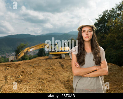 portrait of young caucasian female engineer on construction site with excavator in background - Stock Photo