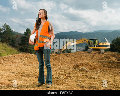female engineer worker on construction site outdoors with excavator in background - Stock Photo