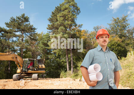 side view of standing engineer holding blueprints on construction site outdoors, with excavator in background - Stock Photo