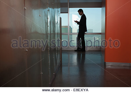 Businessman using cell phone in office - Stock Photo