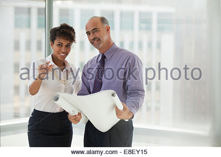 Businessman examining blueprints in office stock photo How do you read blueprints