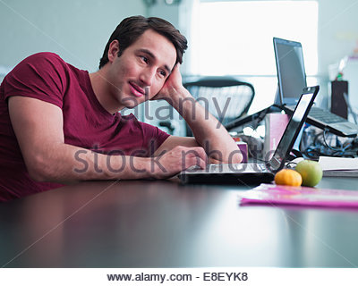 Smiling businessman using laptop and leaning on desk in office - Stock Photo