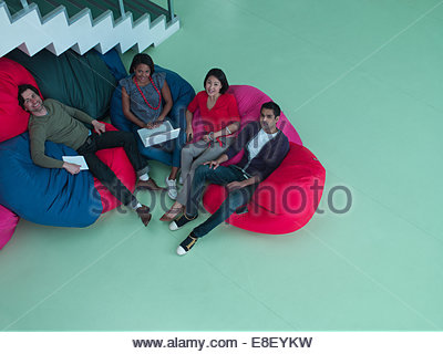 Smiling business people sitting in bean bag chairs - Stock Photo