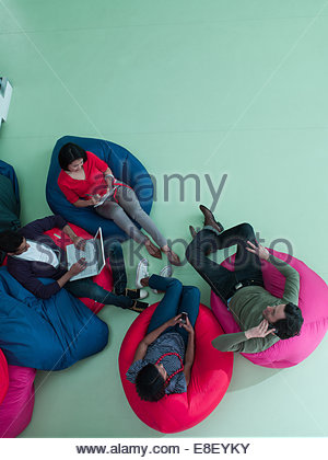 Men and women using laptop and cell phones in bean bag chairs - Stock Photo