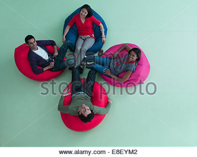 Smiling men and women  bean bag chairs - Stock Photo
