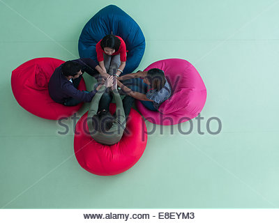 Smiling business people sitting in bean bag chairs with stacked hands - Stock Photo