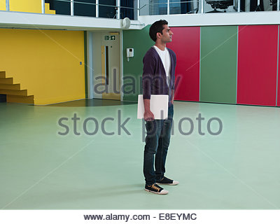Man holding laptop in empty office - Stock Photo