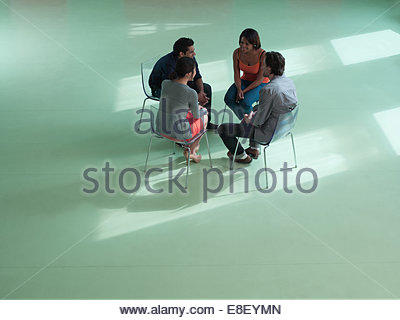Business people sitting in circle - Stock Photo