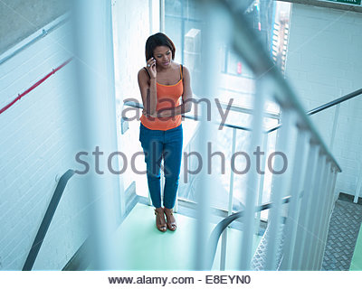 Smiling woman talking on cell phone in stairway - Stock Photo
