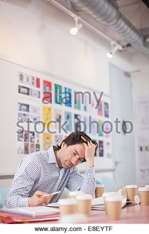 Businessman with head in hands surrounded by coffee cups in office - Stock Photo