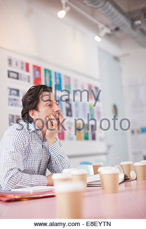 Businessman surrounded by coffee cups in office - Stock Photo