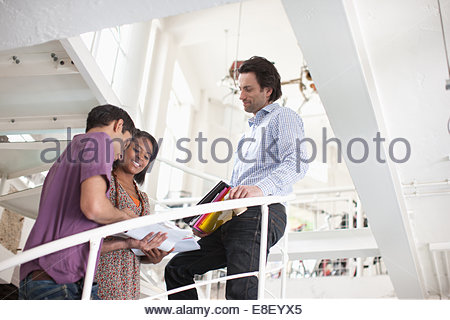 Smiling business people talking on stairs - Stock Photo