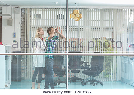 Smiling man and woman looking out window - Stock Photo