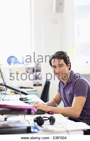 Smiling businessman working on laptop at desk in office - Stock Photo