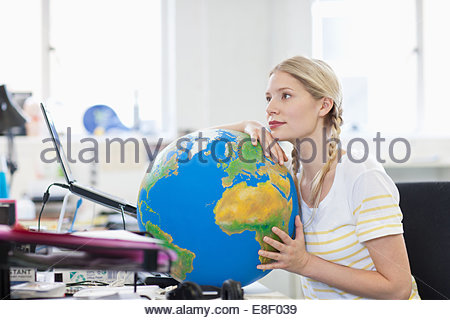 Pensive businesswoman leaning on globe at desk in office - Stock Photo