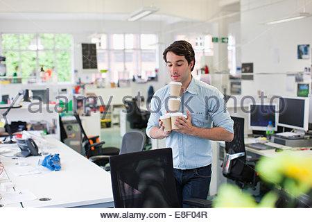 Businessman balancing coffee cups - Stock Photo