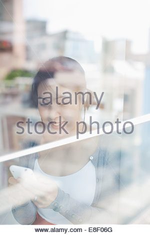 Smiling businesswoman text messaging on cell phone - Stock Photo
