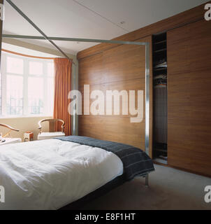 metal fourposter bed with white duvet and gray throw in modern bedroom with wood paneled doors