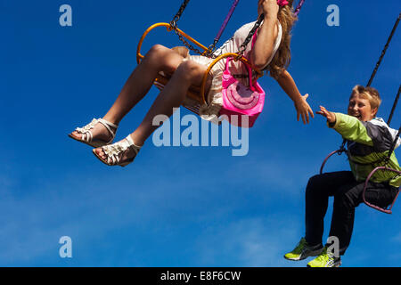 young people on the chain swing carousel, village fair, Czech Republic - Stock Photo