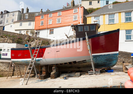 Traditional wooden fishing boat being repaired whilst out of the water on the beach at Mevagissey harbour, Cornwall, - Stock Photo
