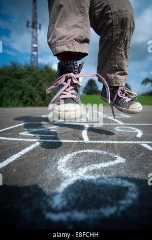 Young girl playing Hopscotch. - Stock Photo
