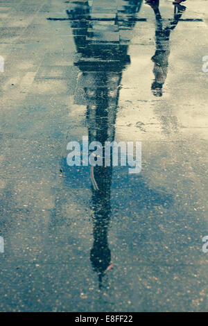 Reflection of man walking past Eiffel Tower in a puddle, Paris, France - Stock Photo