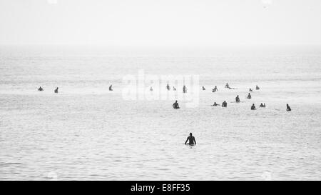 Large group of surfers in ocean waiting to catch a wave - Stock Photo