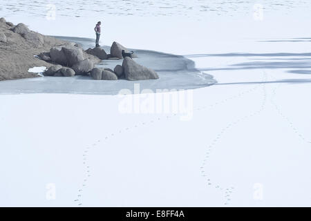 Woman with dog standing by  frozen lake, Colorado, America, USA - Stock Photo