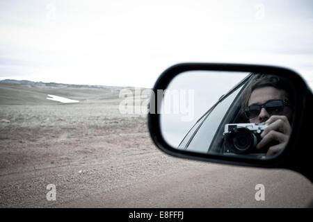 Woman reflecting in side mirror - Stock Photo