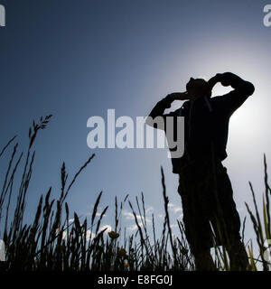 Silhouette of man standing with his arms in the air - Stock Photo