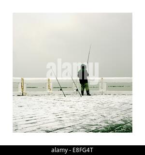 Man standing on pier in winter fishing - Stock Photo