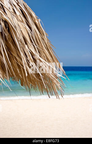 Straw umbrella on tropical beach - Stock Photo