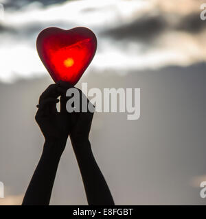 Woman's hands holding a heart shape object - Stock Photo