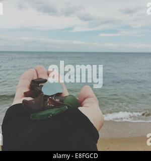 Woman's hand holding pebbles on beach - Stock Photo
