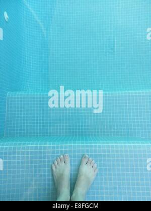 Boy's feet in swimming pool - Stock Photo