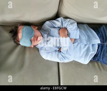 Boy lying on a sofa wearing an eye mask