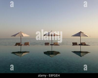 Parasols and sun lounger reflections in a swimming pool - Stock Photo